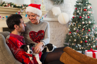 Affectionate couple with dog relaxing in living room with Christmas tree